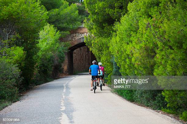 couple cycling on the old railway path - castellon province stock pictures, royalty-free photos & images