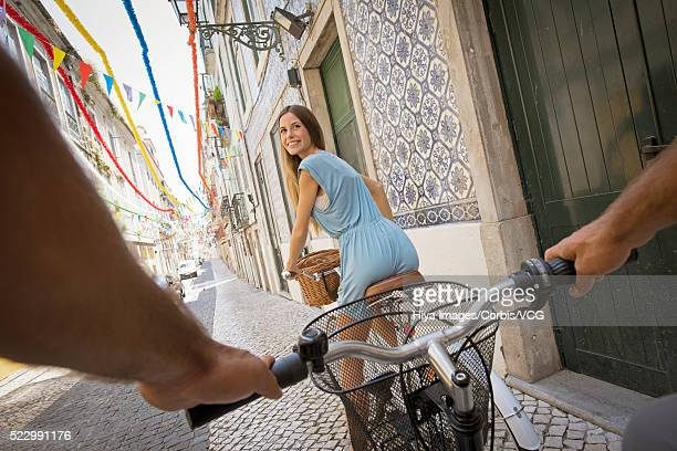Couple cycling through old town, Lisbon, Portugal