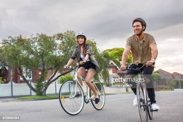 couple cycling through suburban sydney - city life stock pictures, royalty-free photos & images