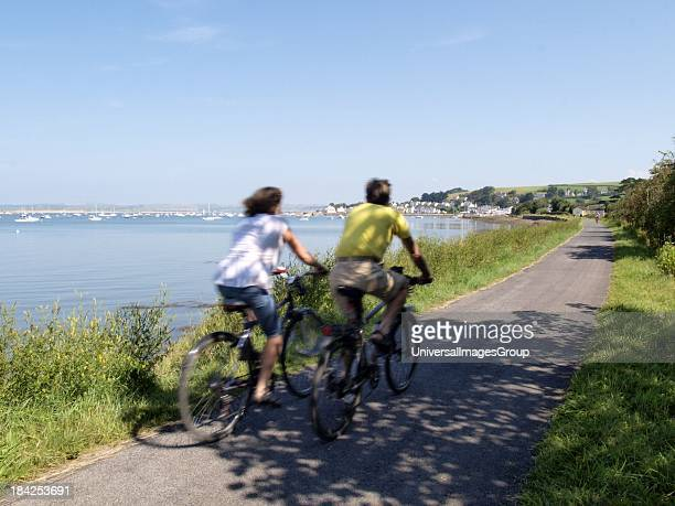 Couple cylcing on the Tarka Trail at Instow, Devon, UK.