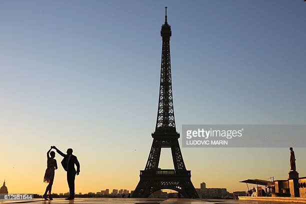 TOPSHOT A couple dance at sunrise on October 6 2016 on the Trocadero plaza in front of the Eiffel towerin Paris / AFP / LUDOVIC MARIN