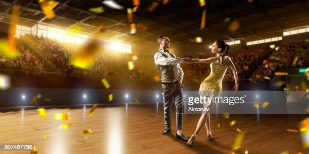 couple dancers ardently perform the latin american dance on a large professional stage with sparkle fireworks - rumba stock photos and pictures