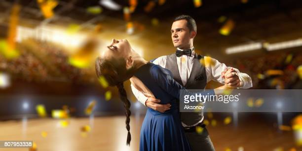 couple dancers ardently perform the latin american dance on a large professional stage with sparkle fireworks - cha cha stock photos and pictures