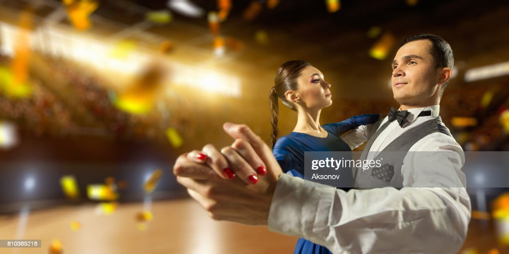 Couple dancers ardently perform the latin american dance on a large professional stage with sparkle fireworks : Stock Photo
