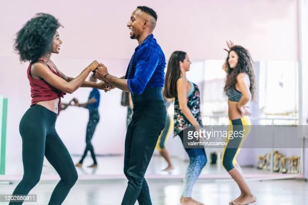 danseurs de couples pratiquant dans le studio, retenant des mains - danse latine photos et images de collection
