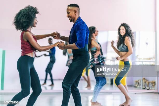 pareja de bailarines practicando en estudio, cogidos de la mano - salsa fotografías e imágenes de stock