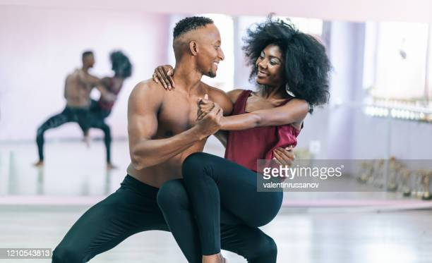 couple dancers practicing in studio, holding hands - professional sportsperson stock pictures, royalty-free photos & images