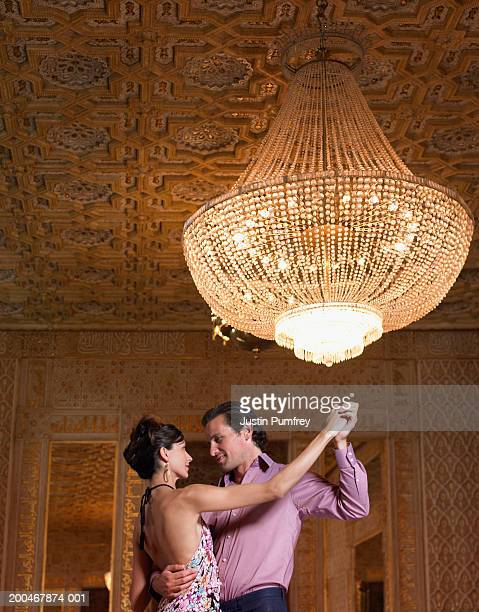 couple dancing beneath chandelier, low angle - gewalt stockfoto's en -beelden