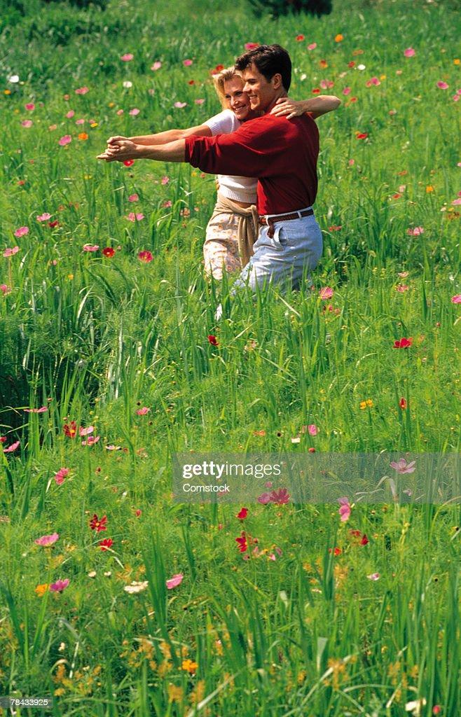 Couple dancing in a field of flowers : Stockfoto