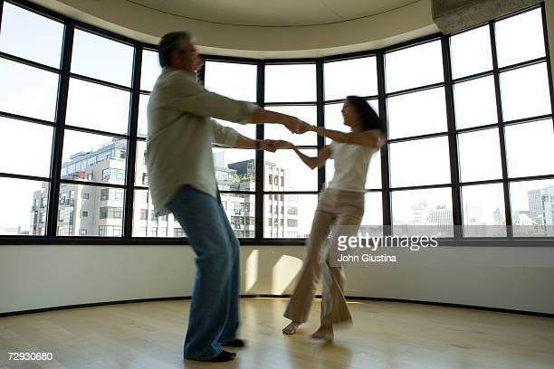 Couple dancing in apartment, blurred motion