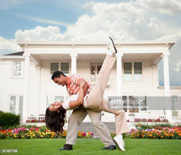 Couple dancing in front of luxury home