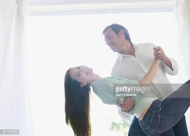 大きな窓の近くのカップルダンス、笑顔