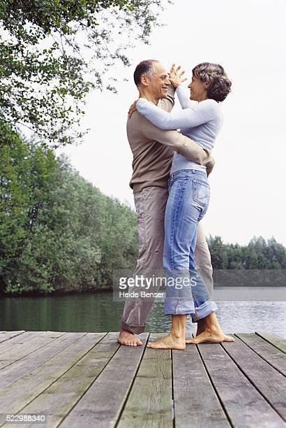 Couple dancing on a dock by a lake