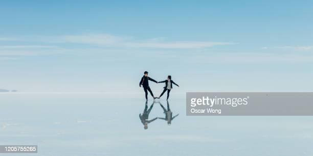 couple dancing on salt flat against sky at salar de uyuni - 世界的な名所 ストックフォトと画像