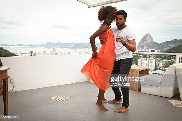 Couple dancing on terrace, Sugarloaf Mountain in background, Rio, Brazil