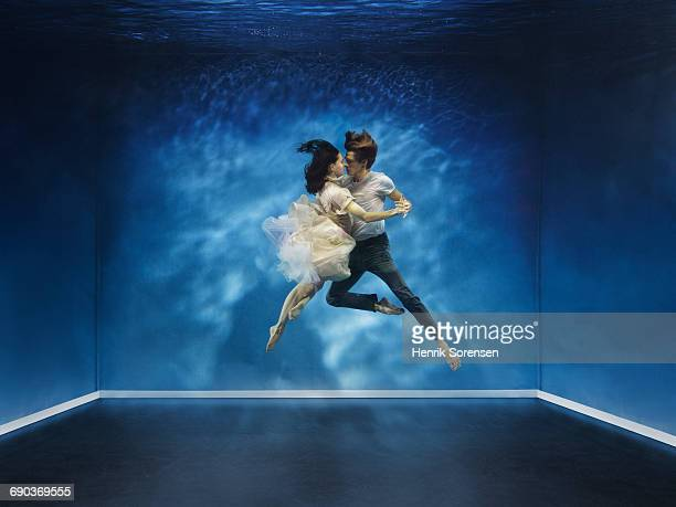 A couple dancing under water