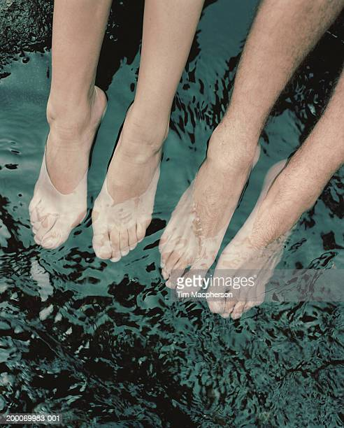 Couple dangling feet in water, low section