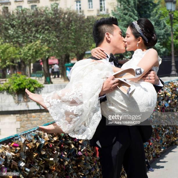 Couple de jeunes mariés s'embrassant devant les cadenas d'amour sur le Pont de l'Archevêché Paris France
