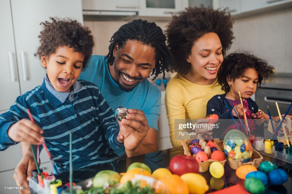 Couple decorating Easter eggs with children : Stock Photo