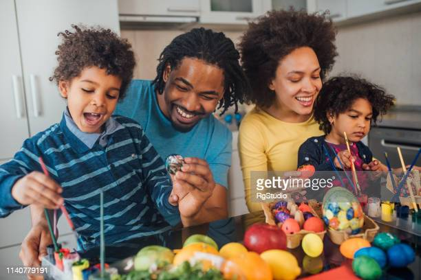 Couple decorating Easter eggs with children