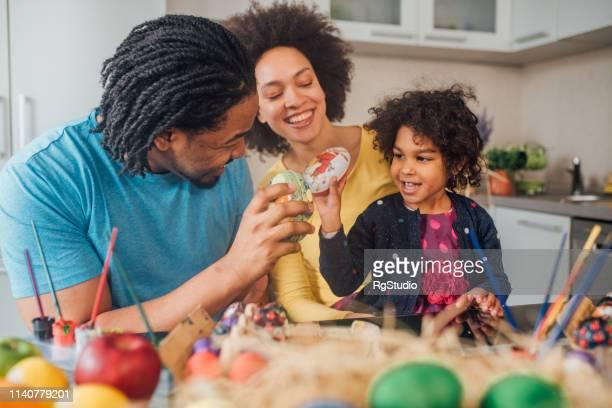 pares que decoram ovos de easter com sua filha - easter family - fotografias e filmes do acervo