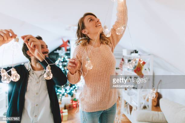 couple decorating for christmas holidays - ornato foto e immagini stock