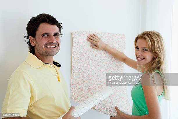 couple decorating new house with wallpaper - wallpaper roll stock pictures, royalty-free photos & images