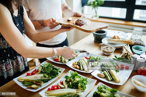 couple decorating plates for dinner party - ディナーパーティー ストックフォトと画像
