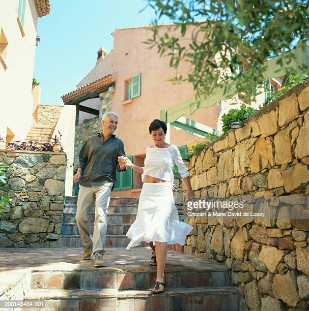 Couple descending steps holding hands, laughing