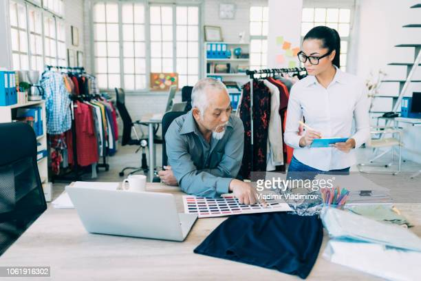 couple designers working in fashion studio - textile factory stock photos and pictures