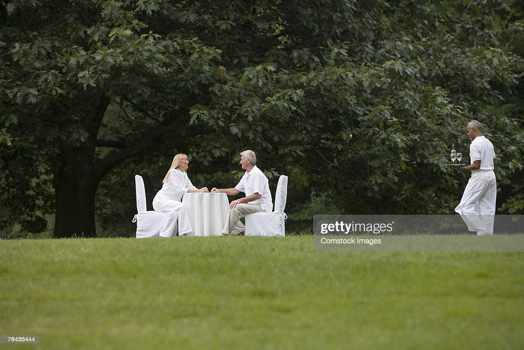Couple dining outdoors as waiter approaches : Stockfoto