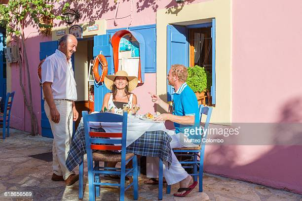 Couple dining outside in a greek village in summer