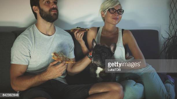 Couple dining pizza with pet