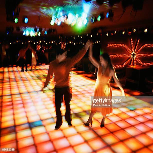 Couple disco dancing on glowing dance floor