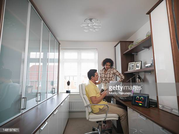 Couple discussing energy bills in home office of energy efficient house