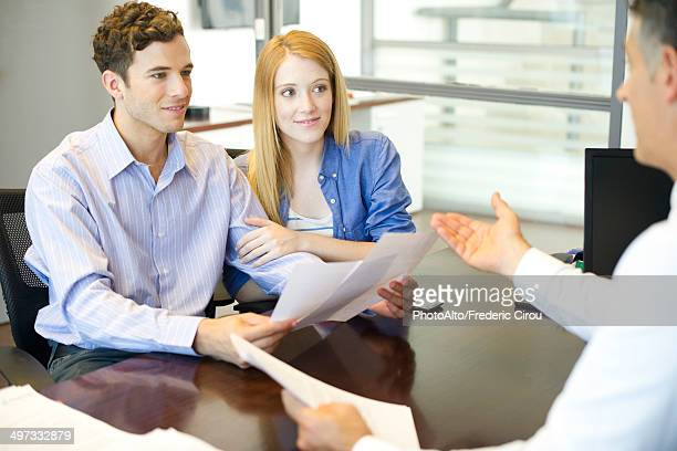 Couple discussing paperwork with advisor