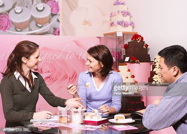 Couple discussing wedding cake with cake maker