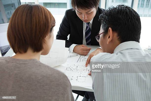 couple discussing with an estate agent their new house plans - real estate office stock photos and pictures