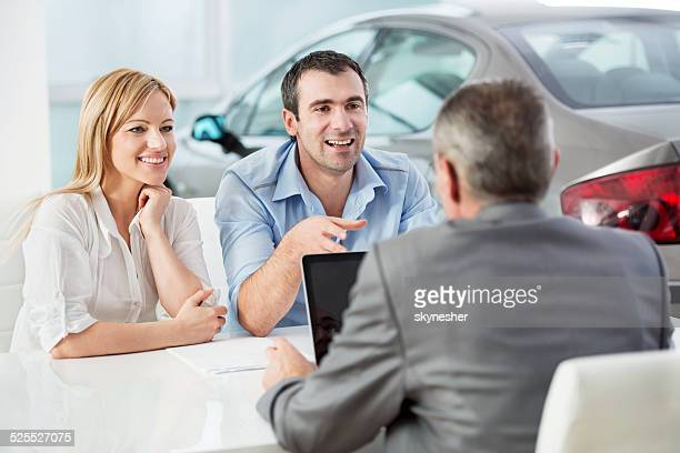 Couple discussing with car salesperson.