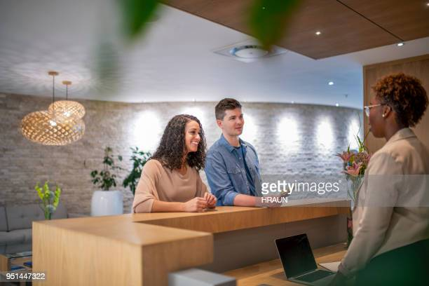 couple discussing with female manger at lobby - tourist resort stock pictures, royalty-free photos & images