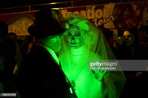 A couple disguised as Catrina walk during the celebration of the day of dead in Guadalajara City on November 01 2014 La Catrina is the Mexican...