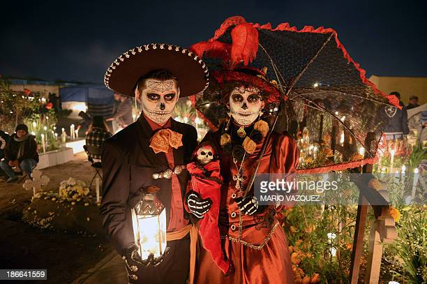 A couple disguised as dead poses at San Jeronimo Chicahualco cemetery in Metepec Mexico on November 2 2013 during the commemoration of the Day of the...