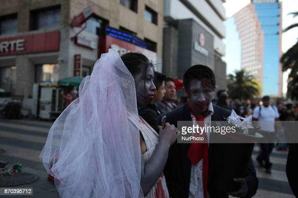 A couple dissgised as a zombie husband and bride during annual procession of zombies in Mexico City on November 4 2017 Hundreds dressed in rags and...