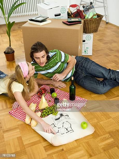 Young couple lying on floor hanving break, looking at plan, elevated view