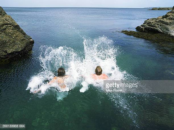 couple diving into water together - northland new zealand stock pictures, royalty-free photos & images
