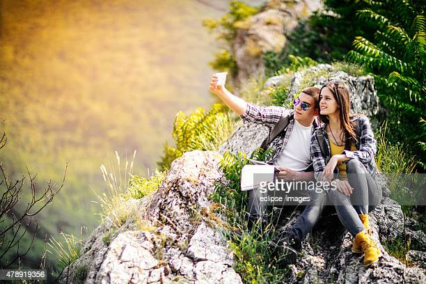 couple doing a selfie on top of the mountain