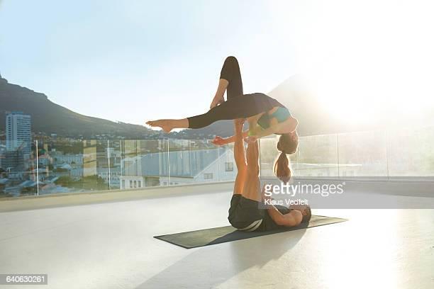 Couple doing acrobatic yoga on rooftop terrace