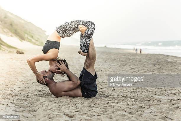 Couple doing Acroyoga on beach