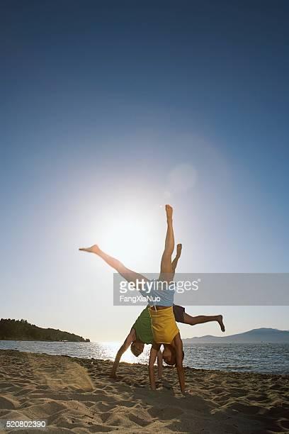 Couple doing cartwheels on the beach