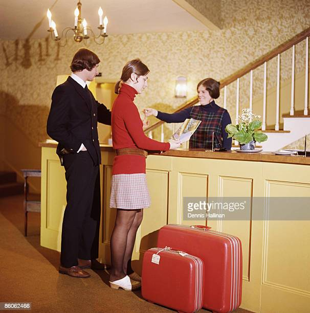 Couple doing check-in at hotel reception desk